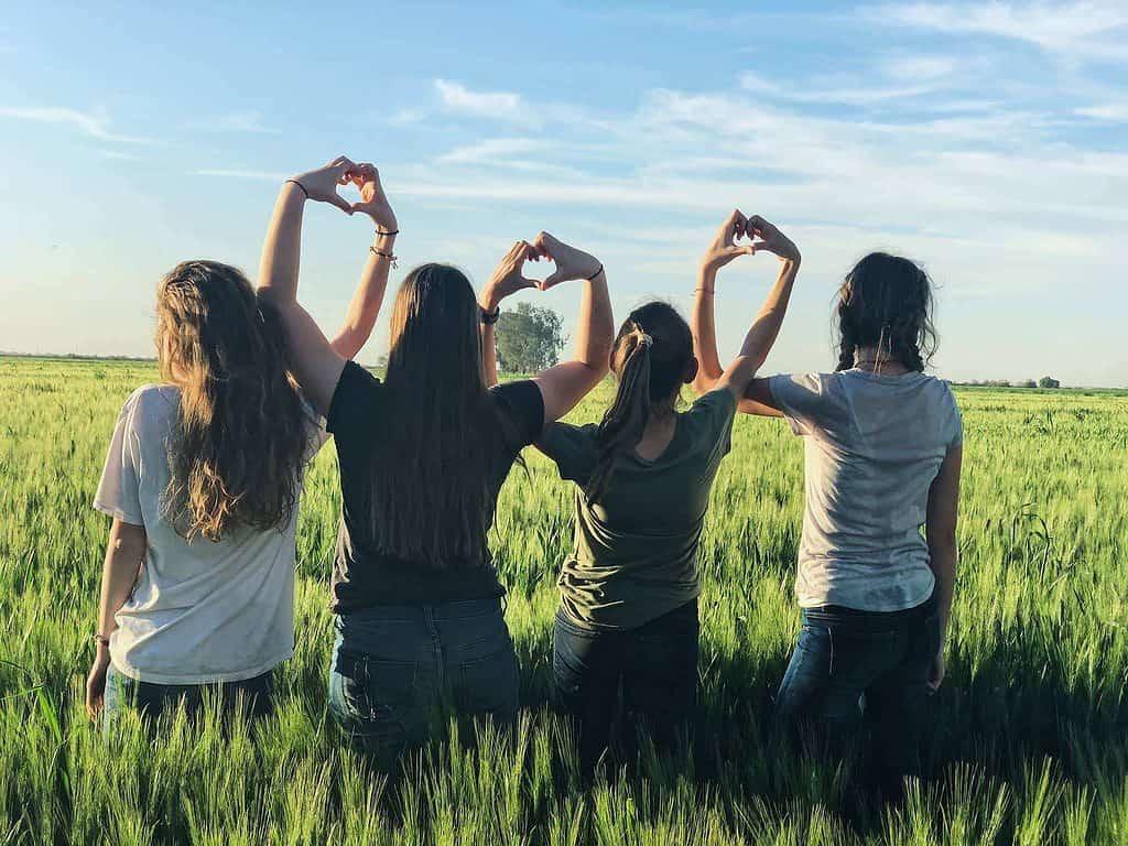 des jeunes filles font des cœurs avec leurs doigts
