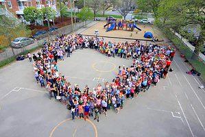 L'équipe-école et les élèves du primaire forment un grand coeur dans la cour du Centre François-Michelle primaire