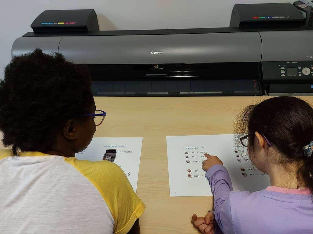 Deux élèves regardent des planches à La Repro FM