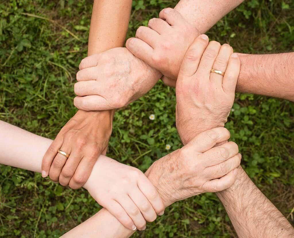 6 mains qui se tiennent le poignet