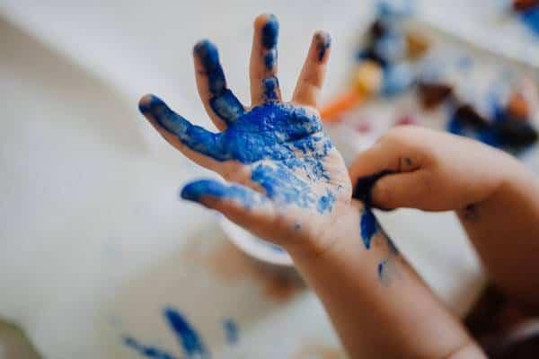 une main d'enfant avec de la peinture bleue