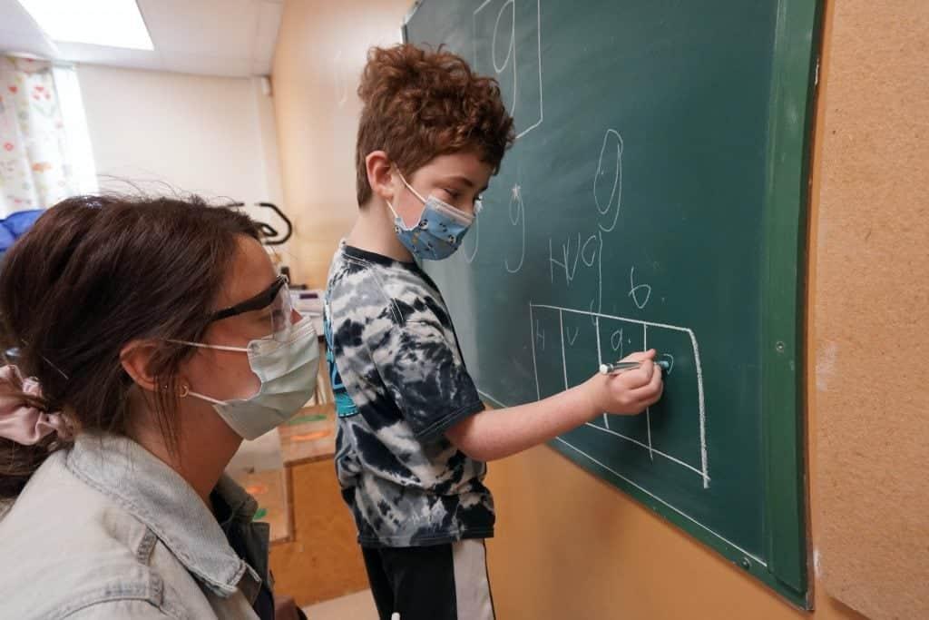 Un élève écrit à la craie sur un tableau d'ardoise