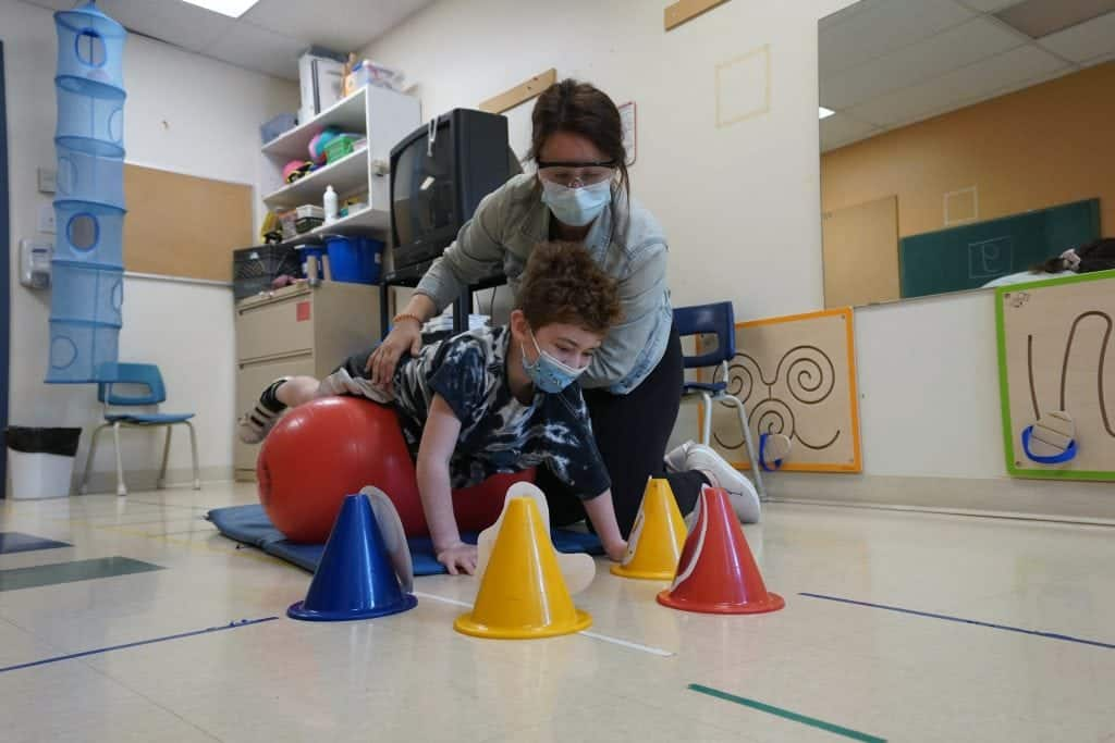 Un élève travaille son équilibre avec une ergothérapeute