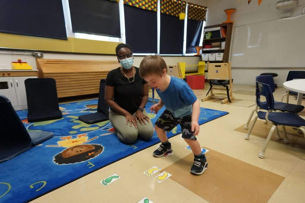 Un élève s'amuse dans une classe avec une éductrice