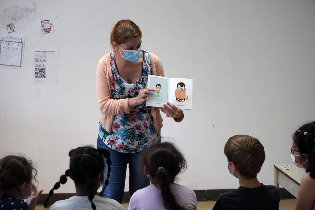 une enseignante fait la lecture à ses élèves