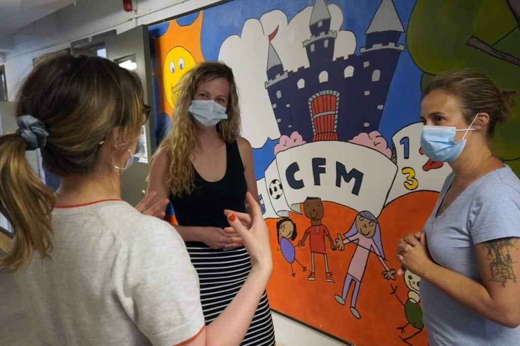 trois membres du personnel discute dans le corridor du CFM primaire