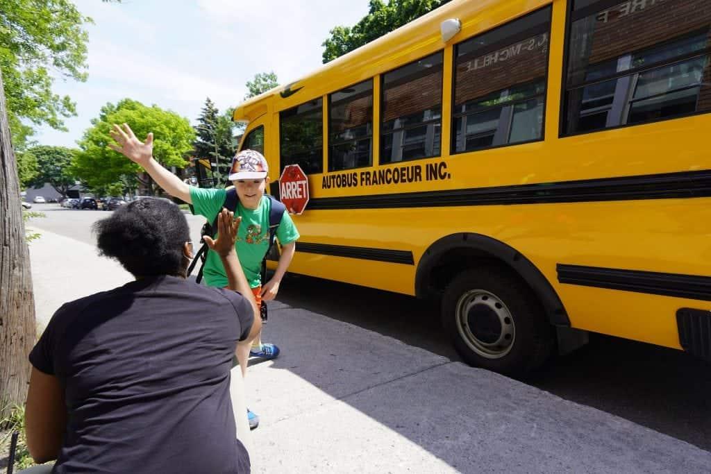 Un élève est accueilli à sa descente de l'autobus scolaire