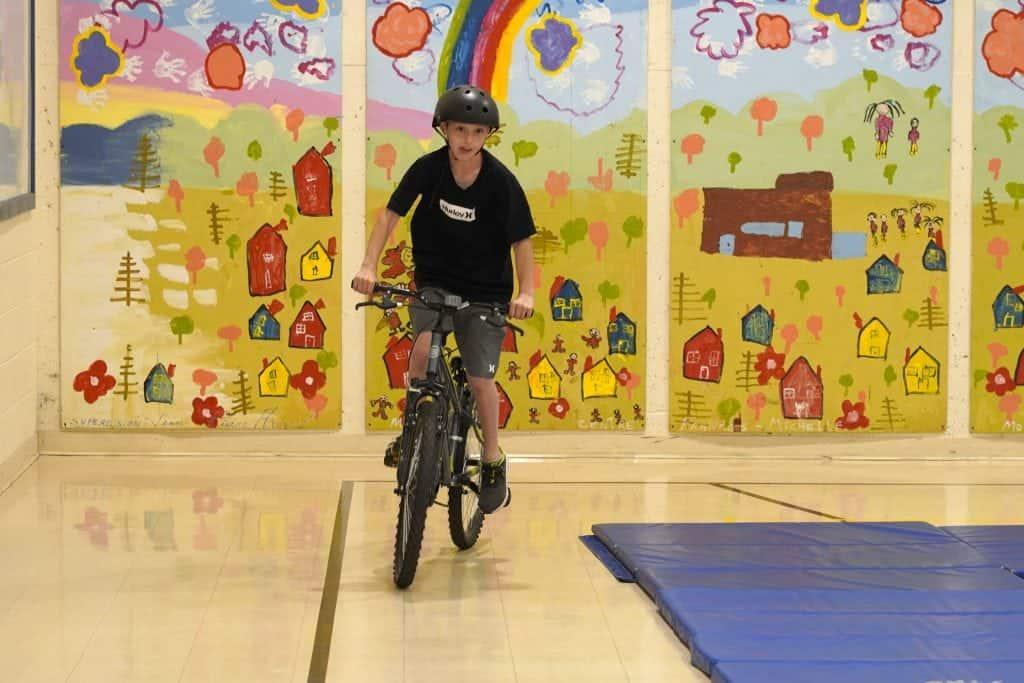 Un élève fait du vélo dans le gymnase du primaire
