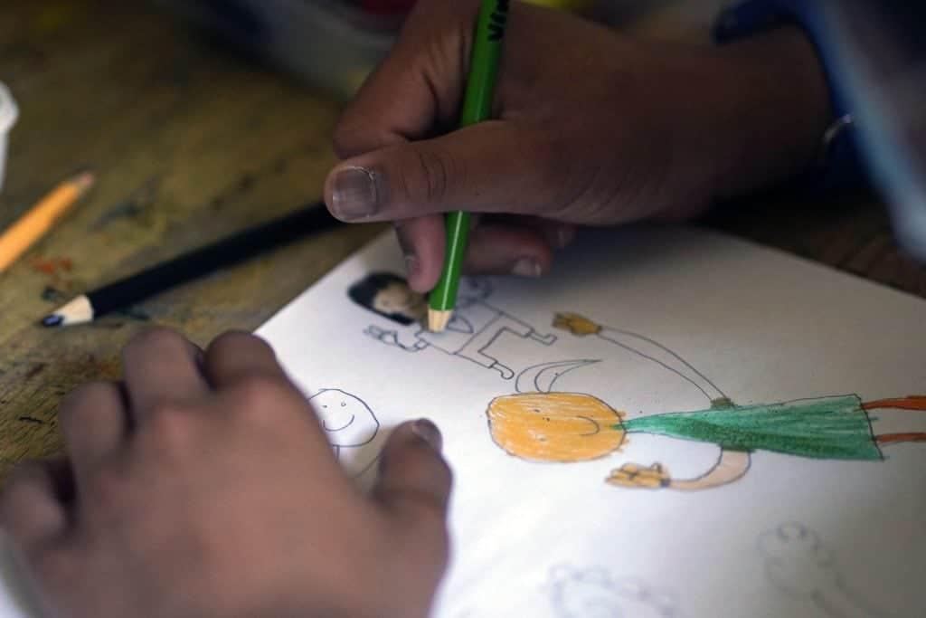 des mains qui dessinent avec des crayons de bois