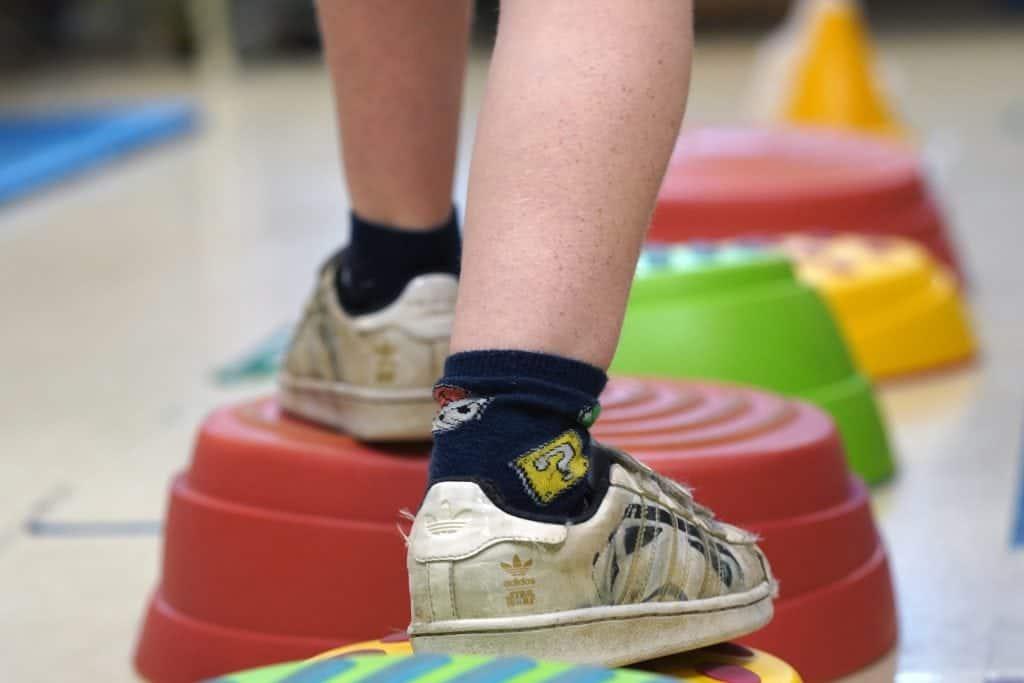 les pieds d'un élève qui fait un parcours d'équilibre