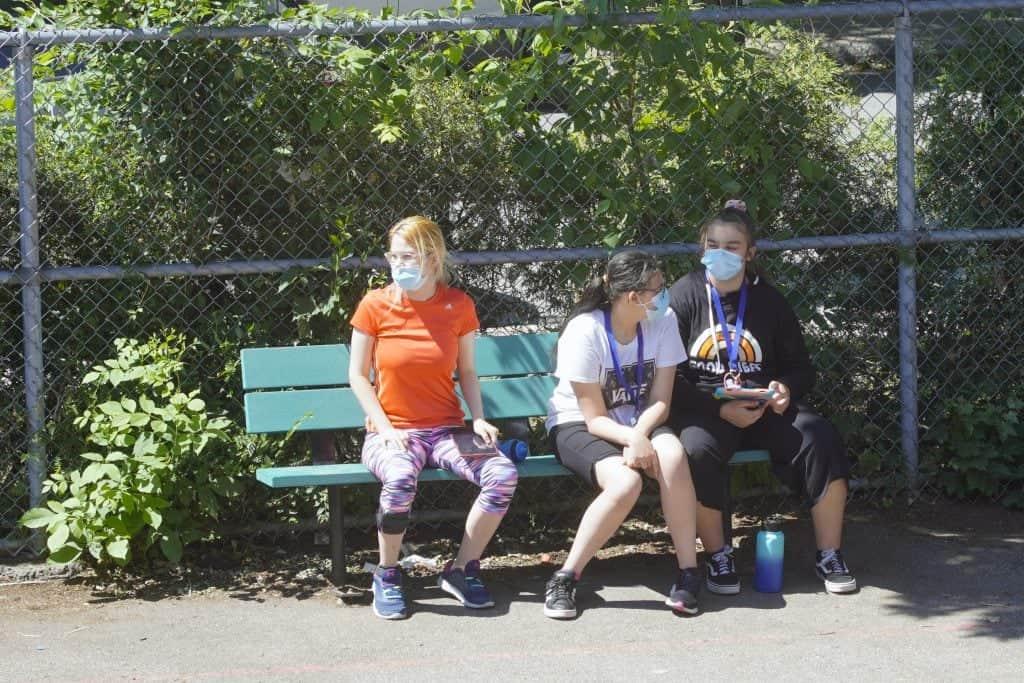 trois élèves sont assises sur un banc dans la cour d'école du secondaire au CFM