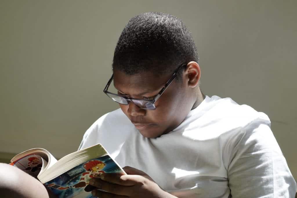 Un élève lit un roman dans sa classe