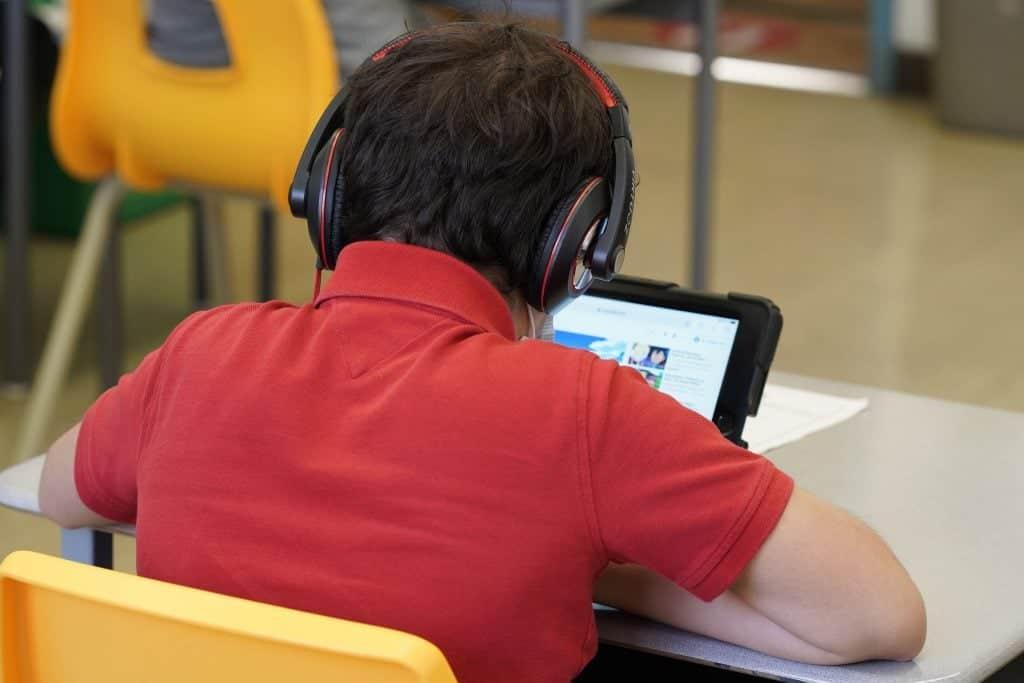 Un élève de dos, à son bureau et devant un Ipad