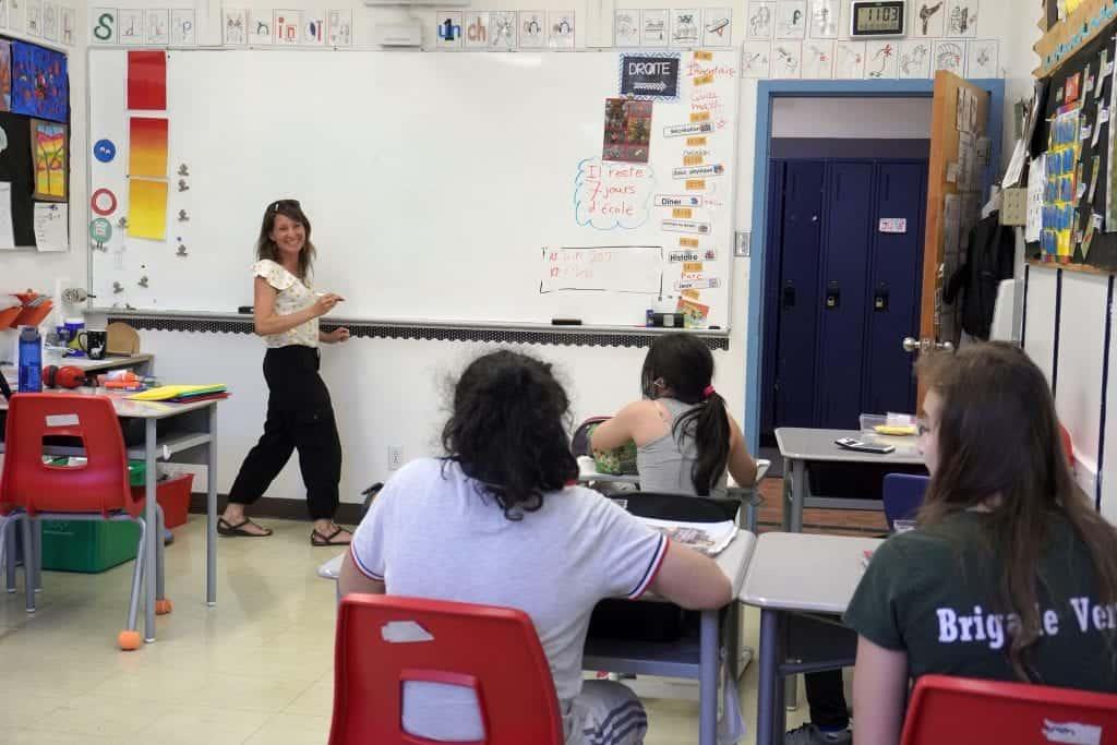 Une enseignante devant un tableau blanc dans sa classe et avec ses élèves