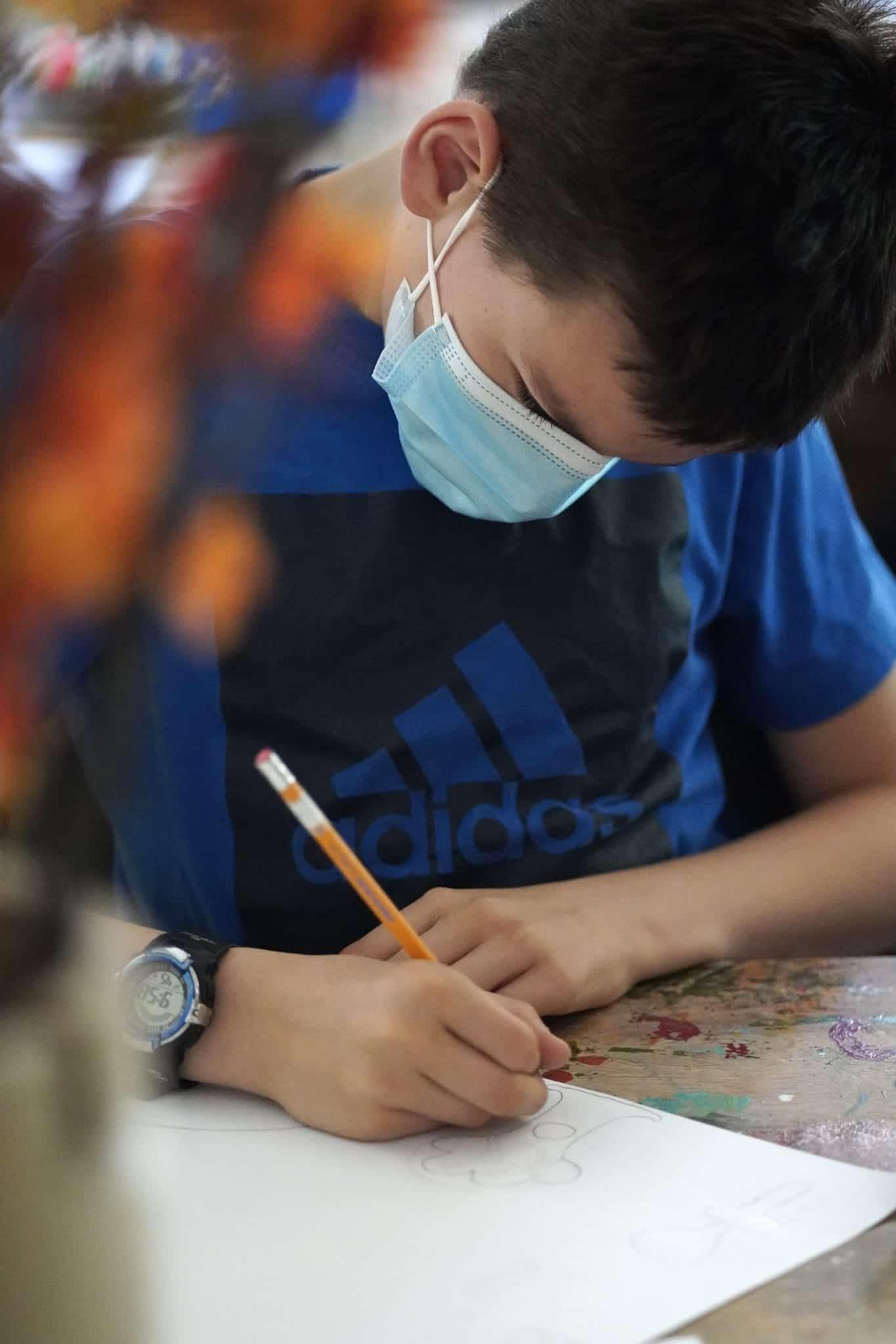 un élève dessine avec un crayon de bois