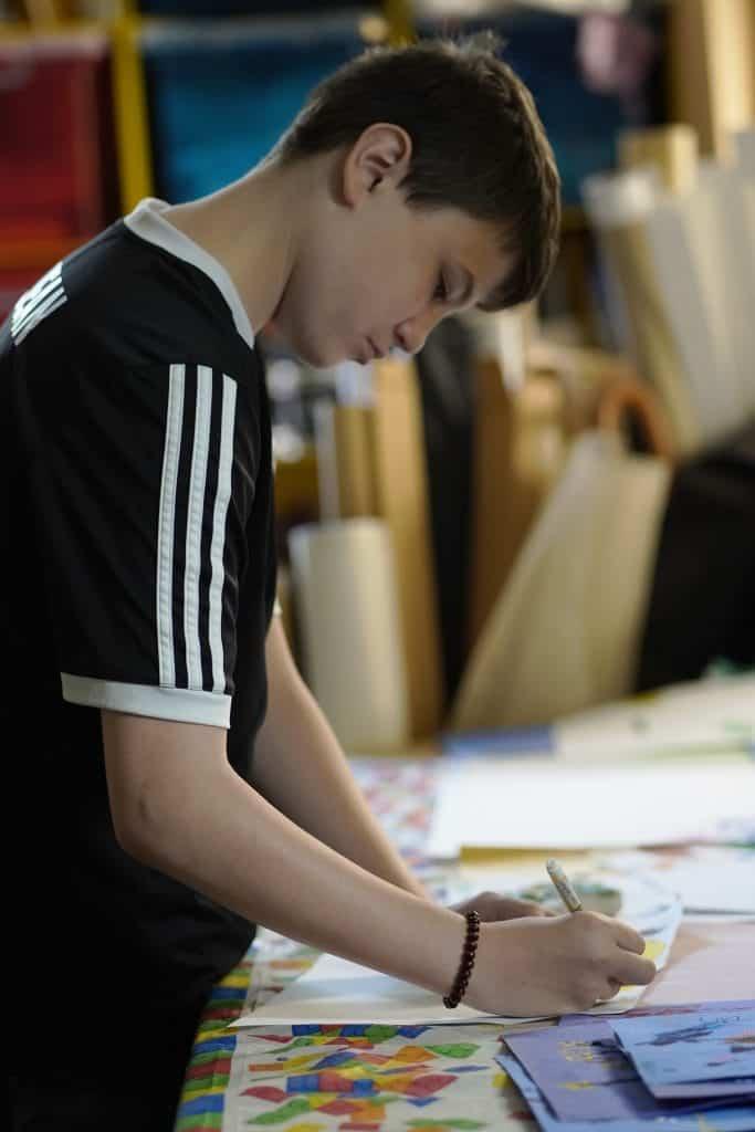 un élève dessine debout