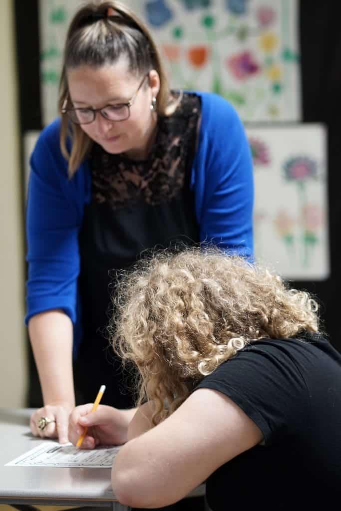 une éducatrice spécialisée accompagne une élève dans un travail