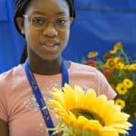une élève prend la pause avec un tournesol dans les mains