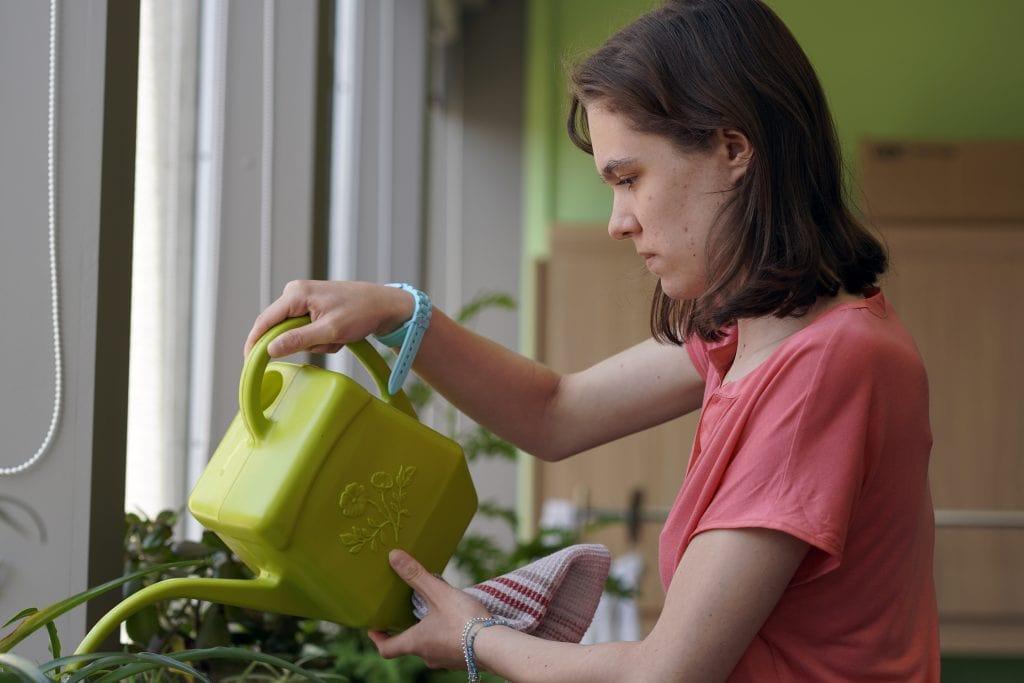 Une élève arrose des plantes à la FPT comme le font les services font les services corporatifs d'entretien de plantes