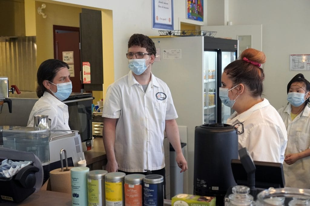 une éducatrice spécialisée discute avec trois élèves de la FPT dans le café-école