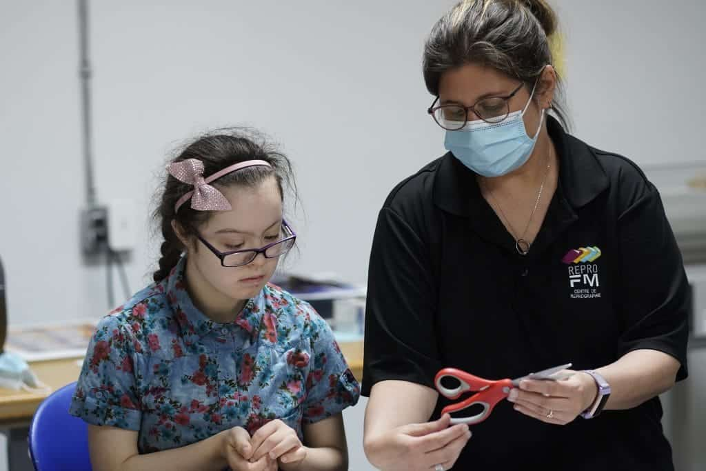 une élève écoute les consignes d'une éducatrice spécialisée à la Repro FM
